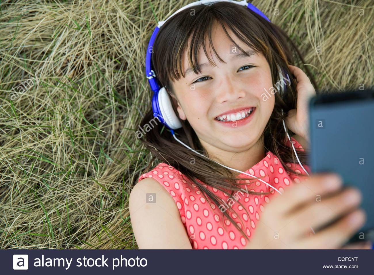 Girl lying down listening to headphones Photo Stock