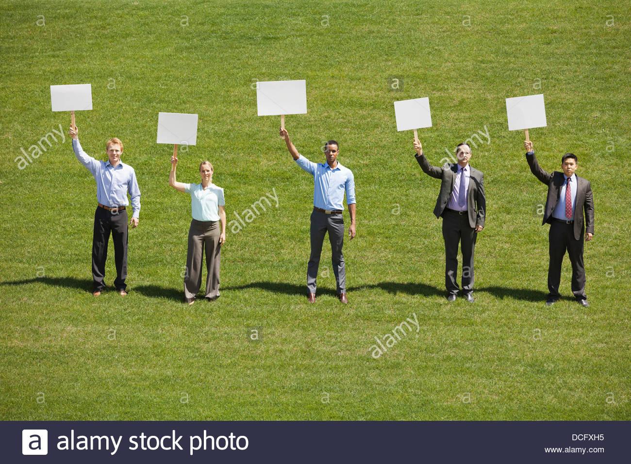 Groupe de gens d'affaires holding blank enseigne à l'extérieur Photo Stock