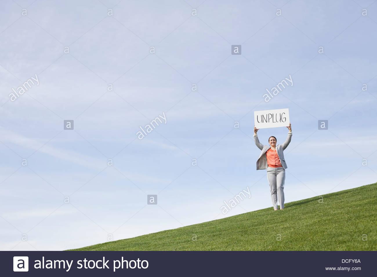 Portrait of businesswoman afficher débranchez pancarte à l'extérieur Photo Stock
