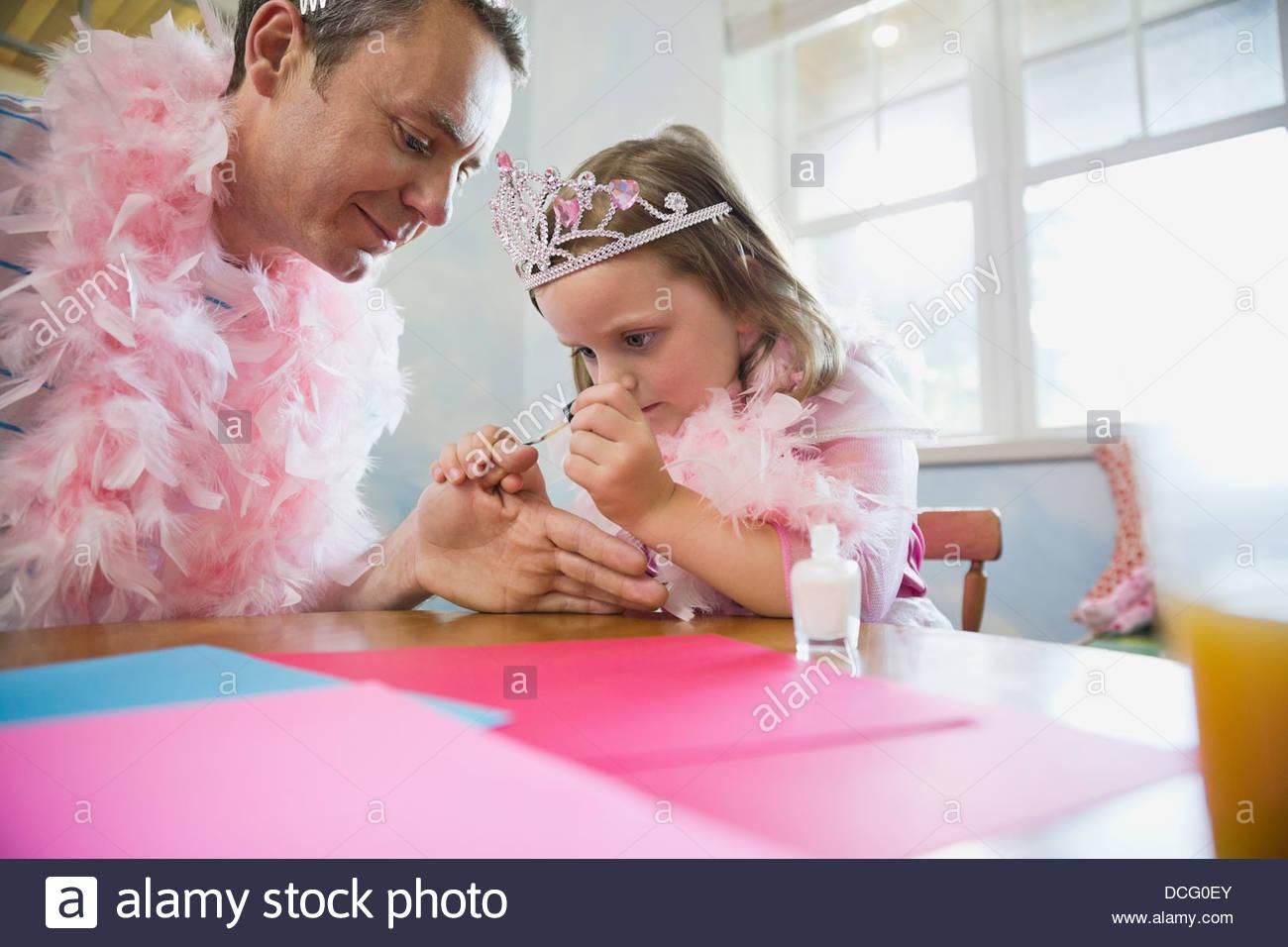 Petite fille peinture ongles pères à table Photo Stock