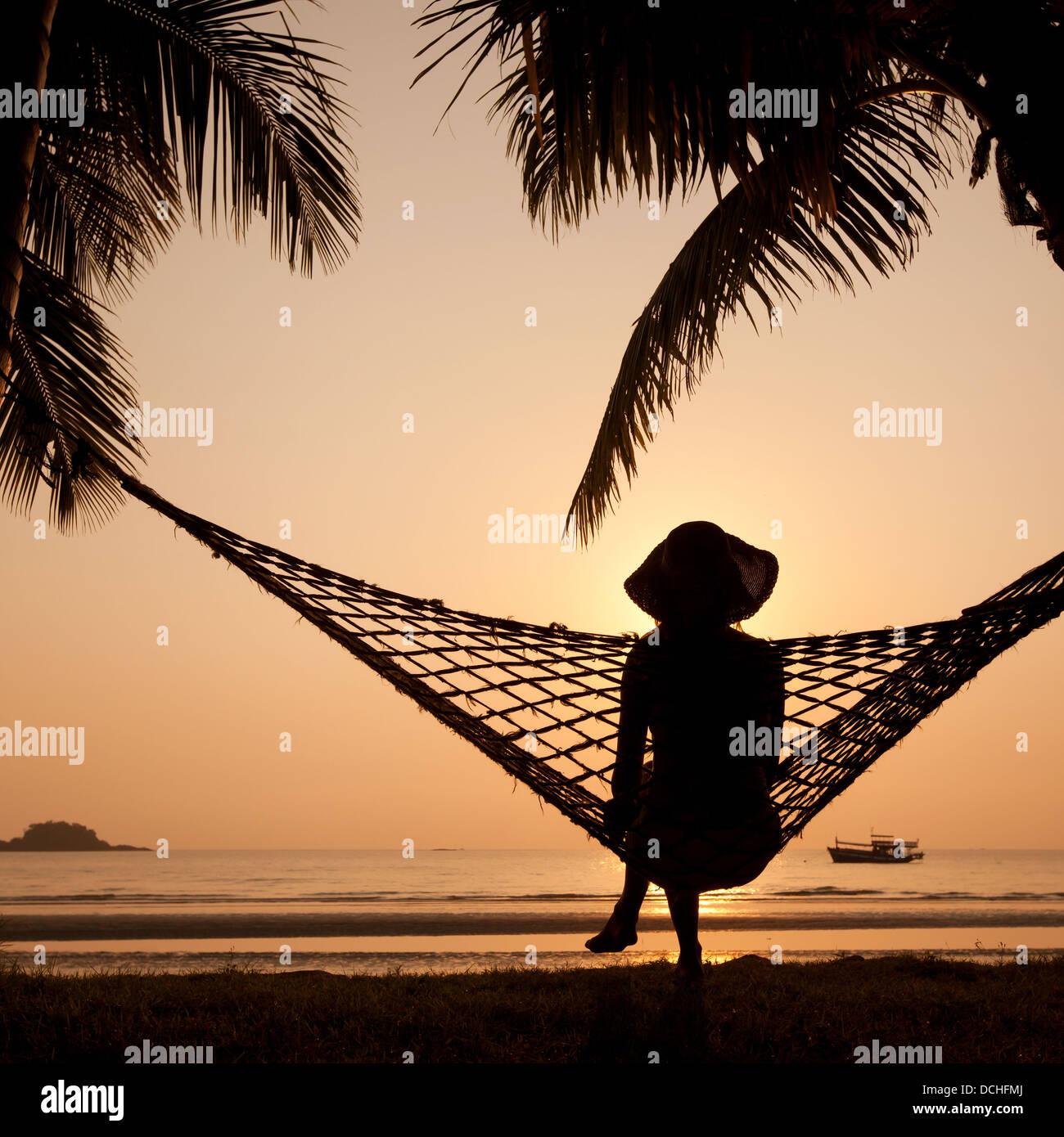 Woman in hammock appréciant le coucher du soleil sur la plage Photo Stock