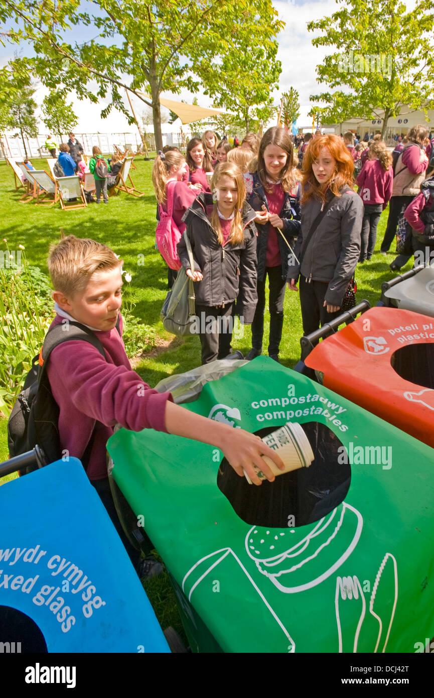 Les enfants de l'école au Hay Festival mettant les contenants de déchets dans un bac de recyclage. Photo Stock