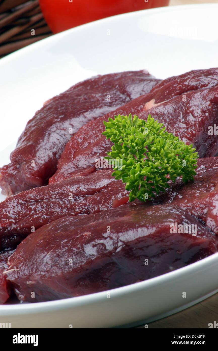 Steak d'autruche brutes de persil sur une assiette Photo Stock
