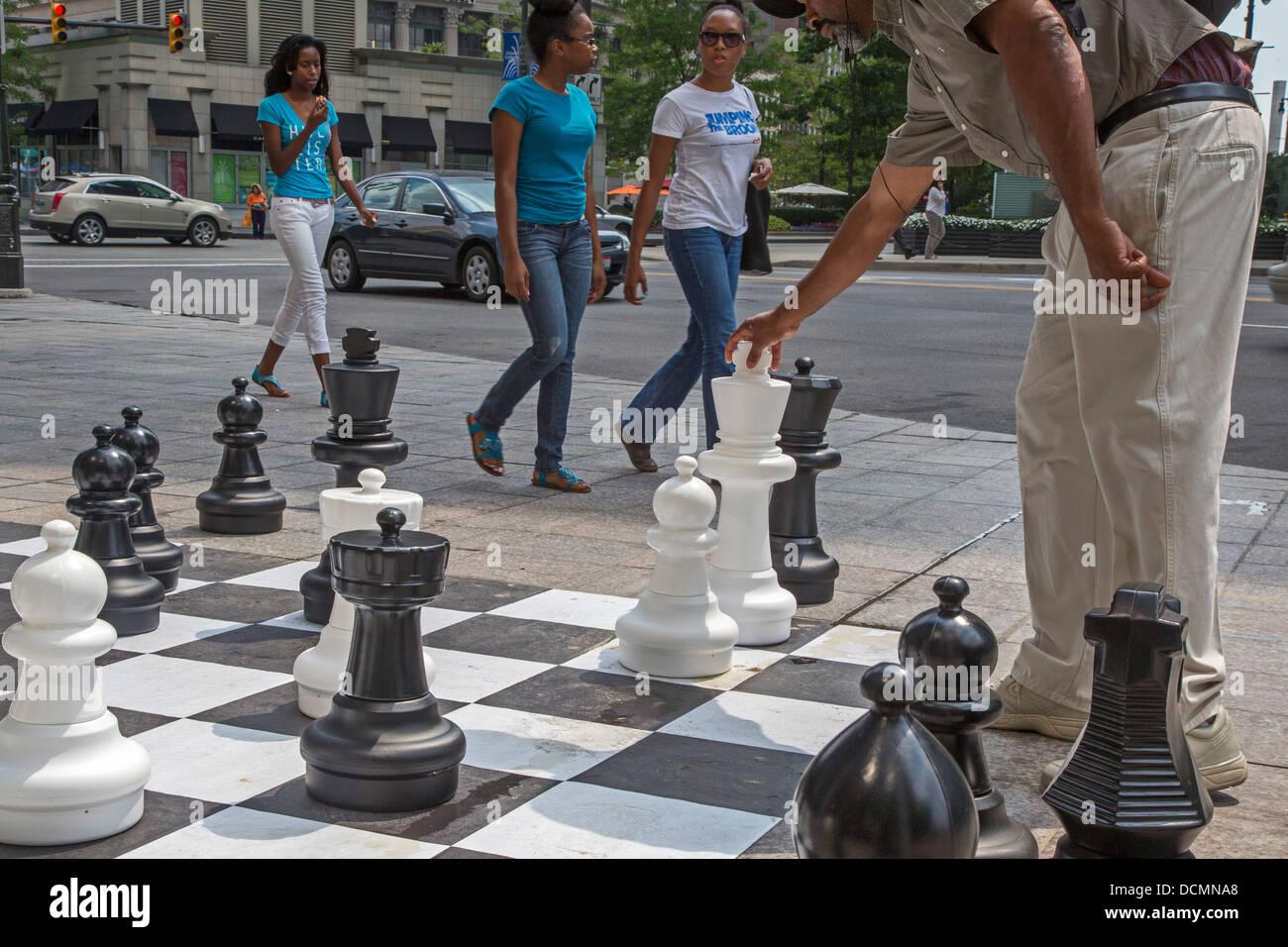 Detroit, Michigan - Un homme se déplace un morceau dans un trottoir d'échecs au centre-ville de Detroit. Banque D'Images