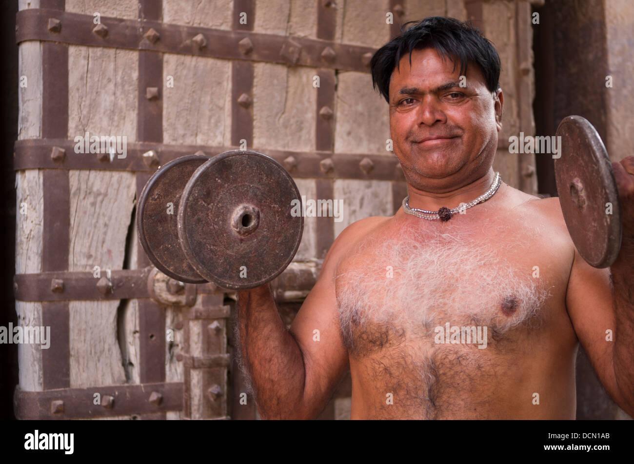 L'homme indien avec formation à l'extérieur des portes de dumbells Meherangarh Fort - Jodhpur, Photo Stock