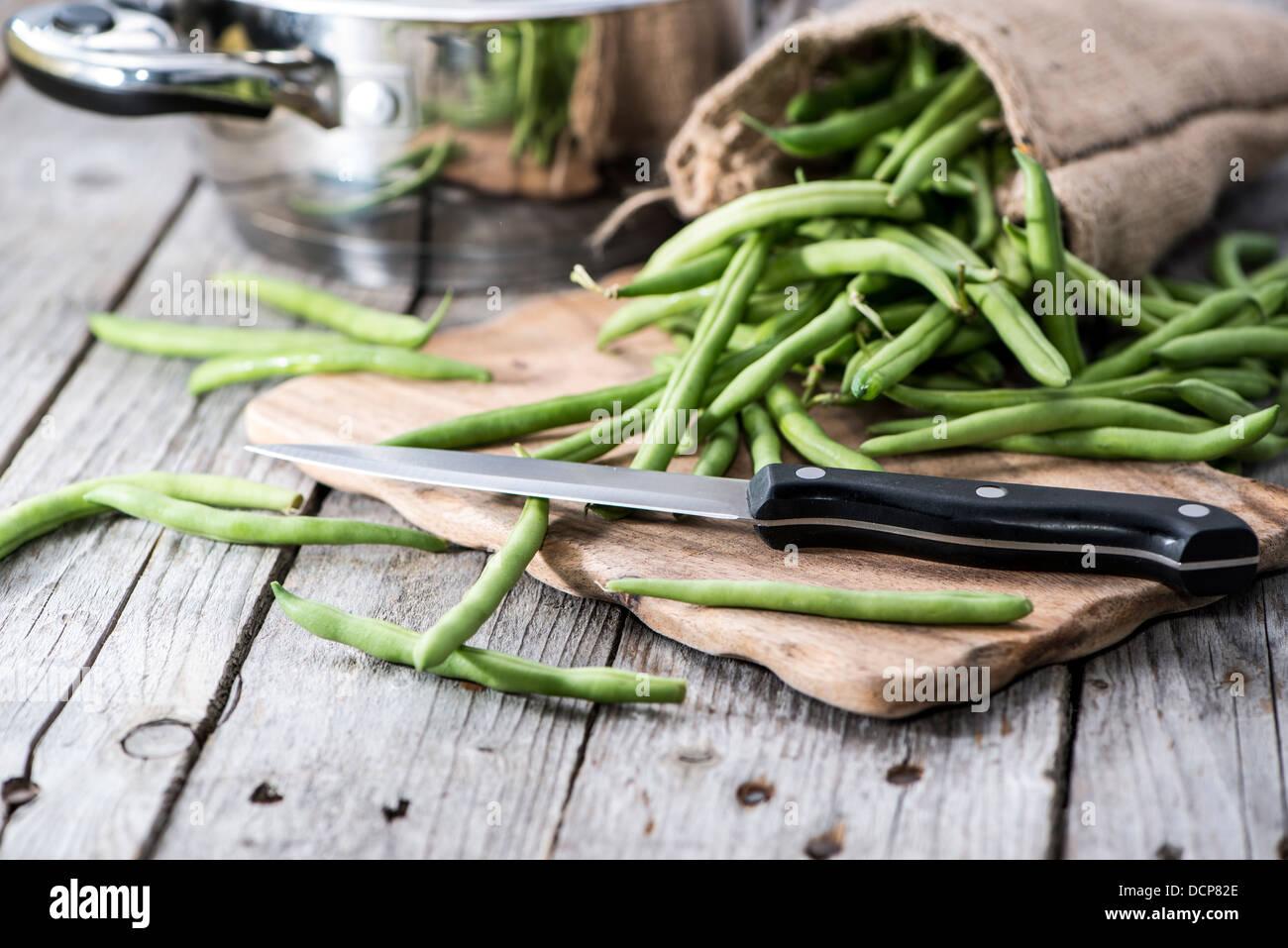 Les Haricots verts sur un fond de bois vintage gris Photo Stock