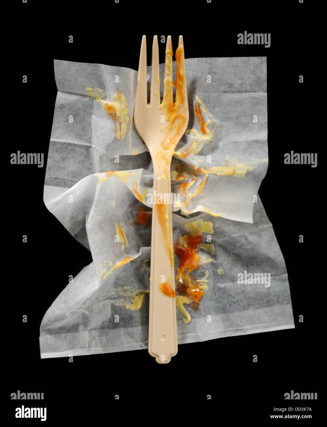 Une fourchette à dîner en plastique sur une serviette de nettoyage froissé. Photo Stock
