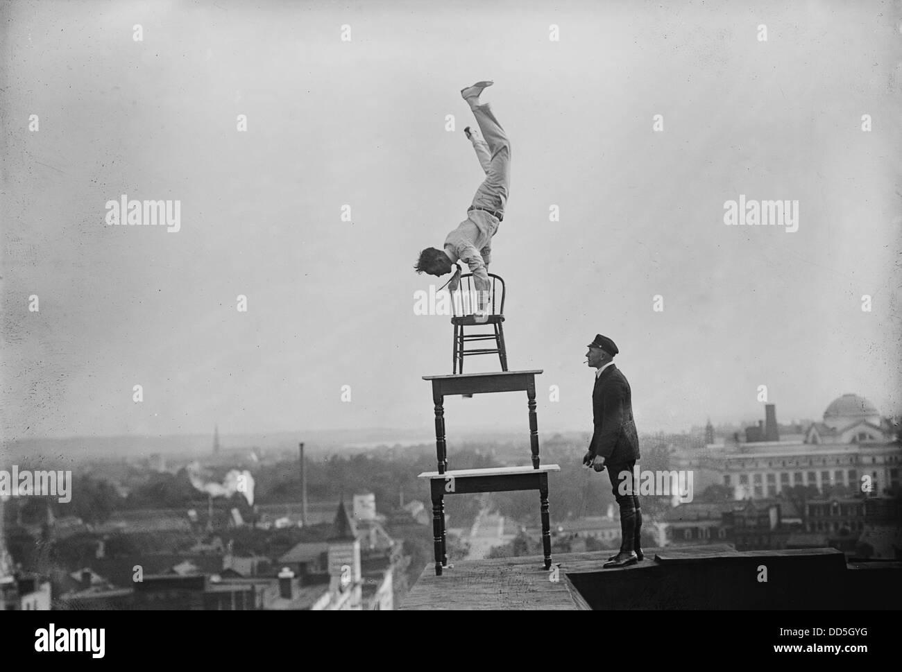 Jammie Reynolds, en équilibre sur le sur des chaises sur le bord d'un toit à Washington, DC CA. 1921 Photo Stock