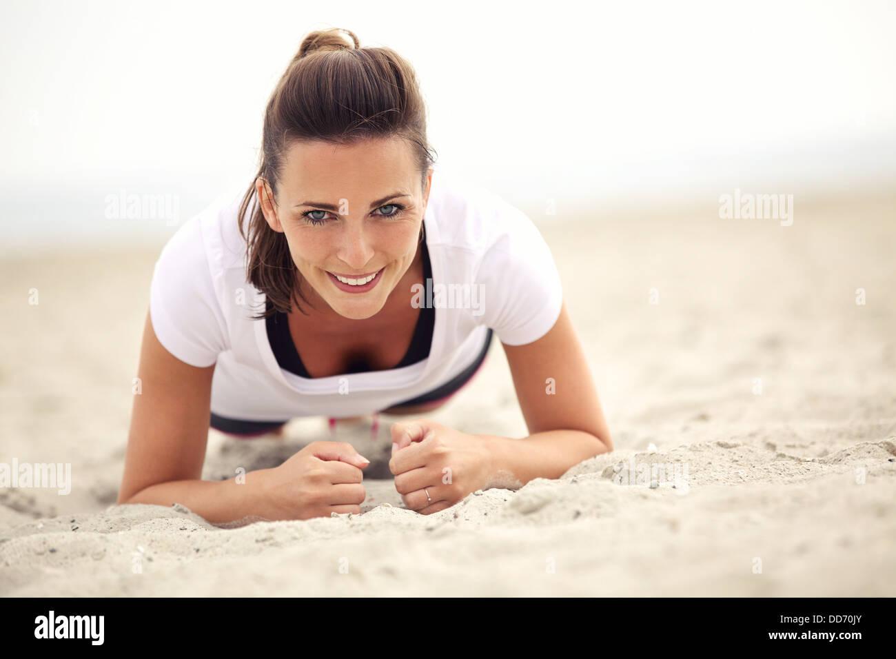 Smiling woman outdoors remise en forme faire de l'exercice sur la plage Photo Stock