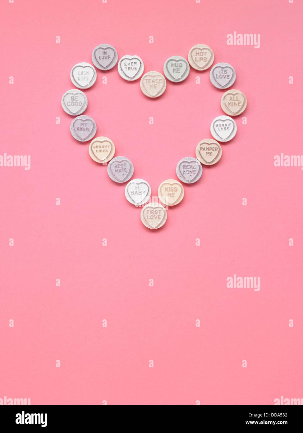 Amour coeur placé en forme de cœur sur un fond rose Photo Stock