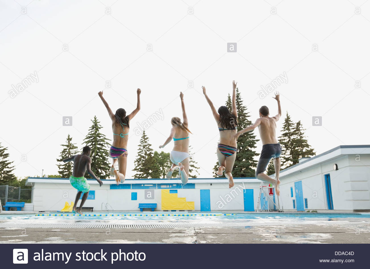 Groupe d'adolescents jumping into swimming pool Banque D'Images