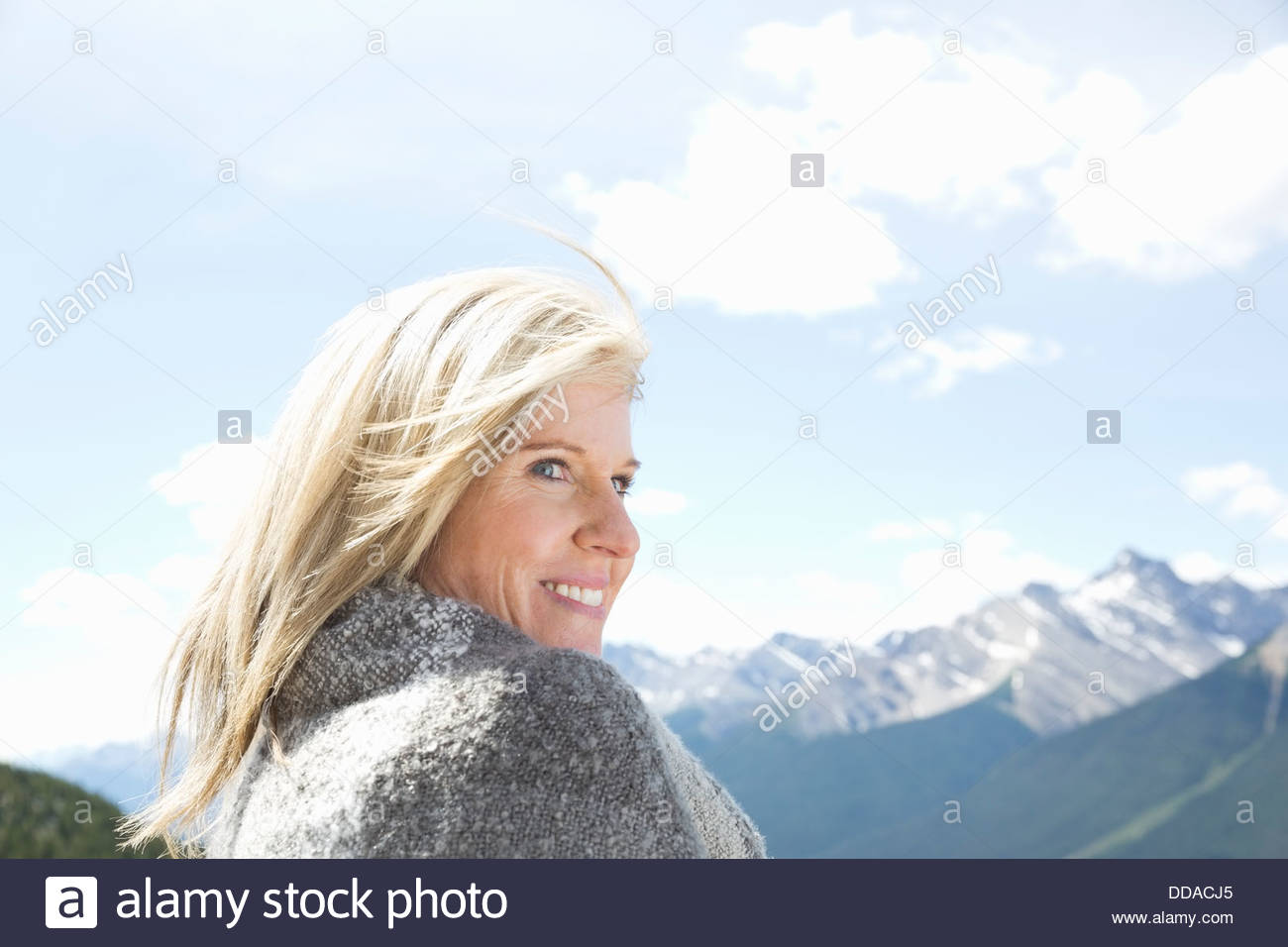 Woman wrapped in blanket contre montagne Photo Stock