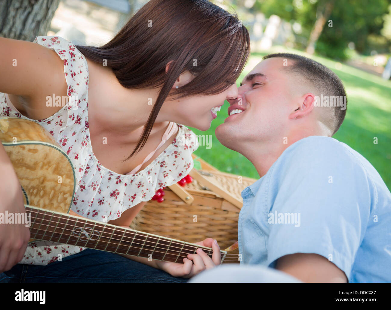 Mixed Race Couple affectueux avec guitare s'embrasser dans le parc. Photo Stock