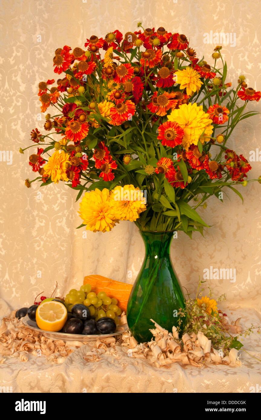 Nature morte avec fleurs jaune vif et orange dans le vase vert avec des fruits Banque D'Images