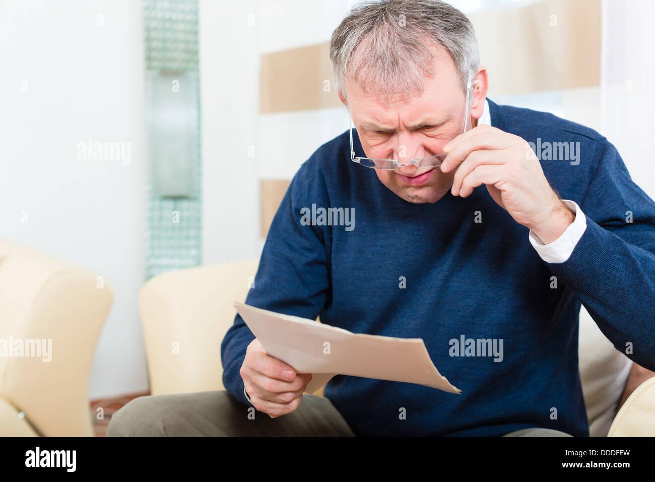 Homme plus âgé ou Senior ont reçu une lettre, peut-être que c'est un rappel ou un projet Photo Stock