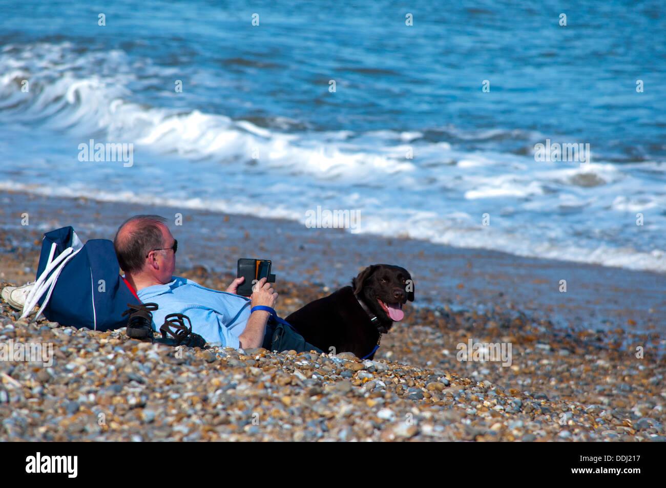 La lecture de l'homme e kindle reader on beach Photo Stock