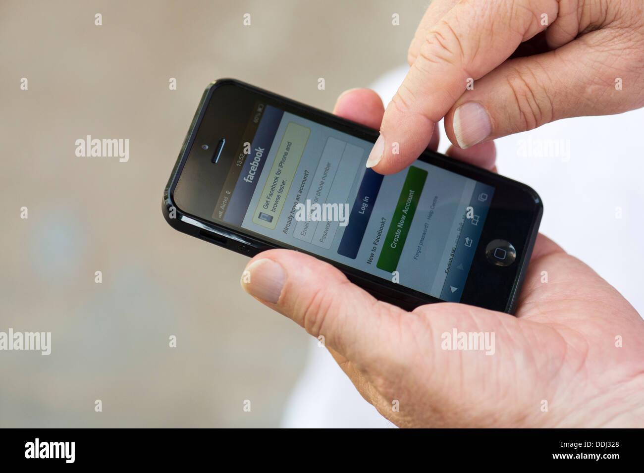 Senior Apple iphone 5 pour vous connecter à Facebook Photo Stock