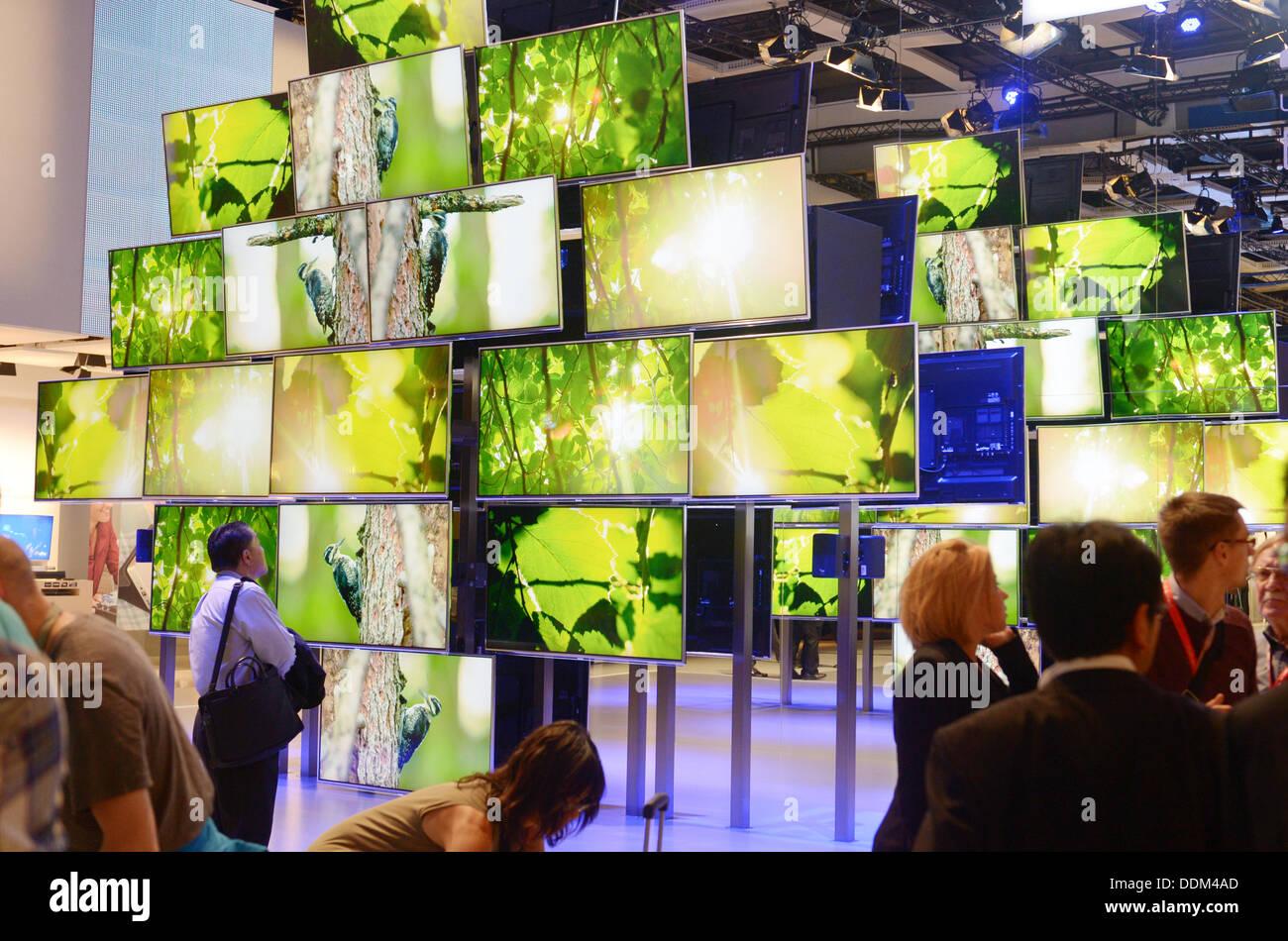 Berlin, Allemagne. 4e août, 2013. Les visiteurs sont devant un mur de téléviseurs 4K au stand de l'électronique Panasonic fabricant au cours de la journée des médias à l'exposition de la radio internationale (IFA) à Berlin, Allemagne, 4 septembre 2013. La technologie 4K pour les téléviseurs est considéré comme un successeur de la politique commune de format HD. L'IFA va avoir lieu du 6 septembre au 11 septembre 2013. Photo: Rainer Jensen/dpa/Alamy Live News Photo Stock