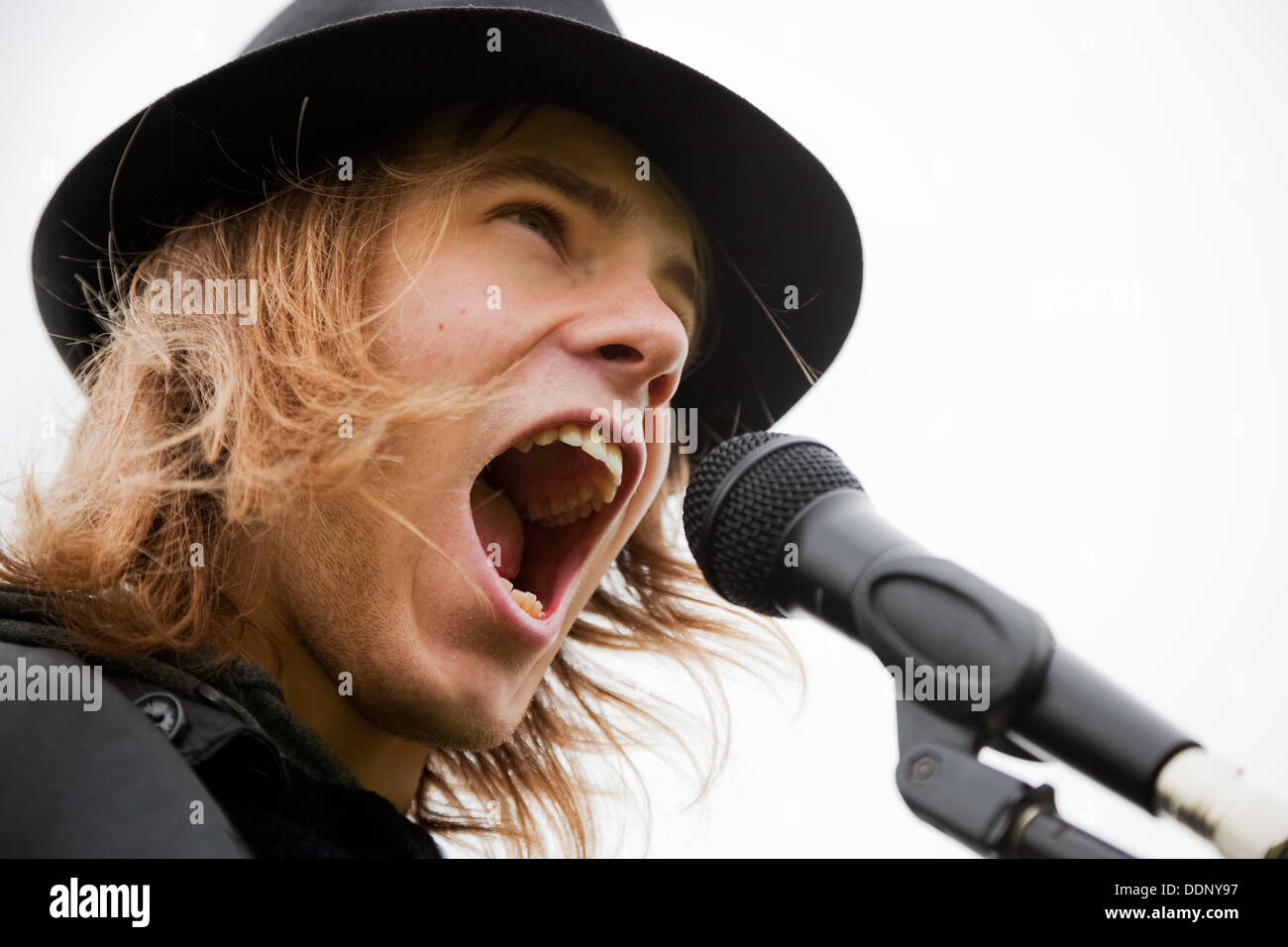 Young man in hat chante pour microphone Photo Stock