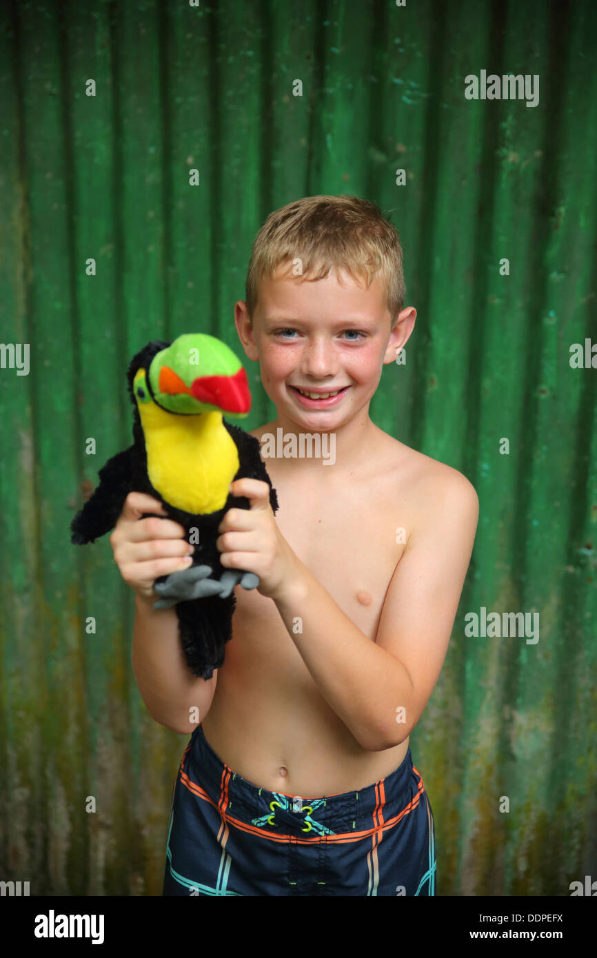 Boy holding toy toucan, Costa Rica Photo Stock