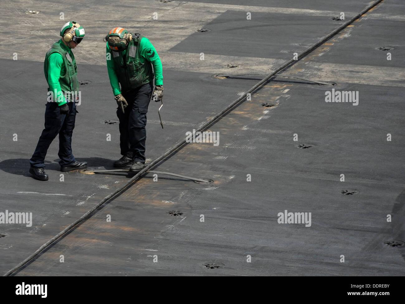 Boatswain's Aviation mates (équipement) inspecter les câbles d'arrêt avant d'opérations de vol à bord du porte-avions USS Photo Stock