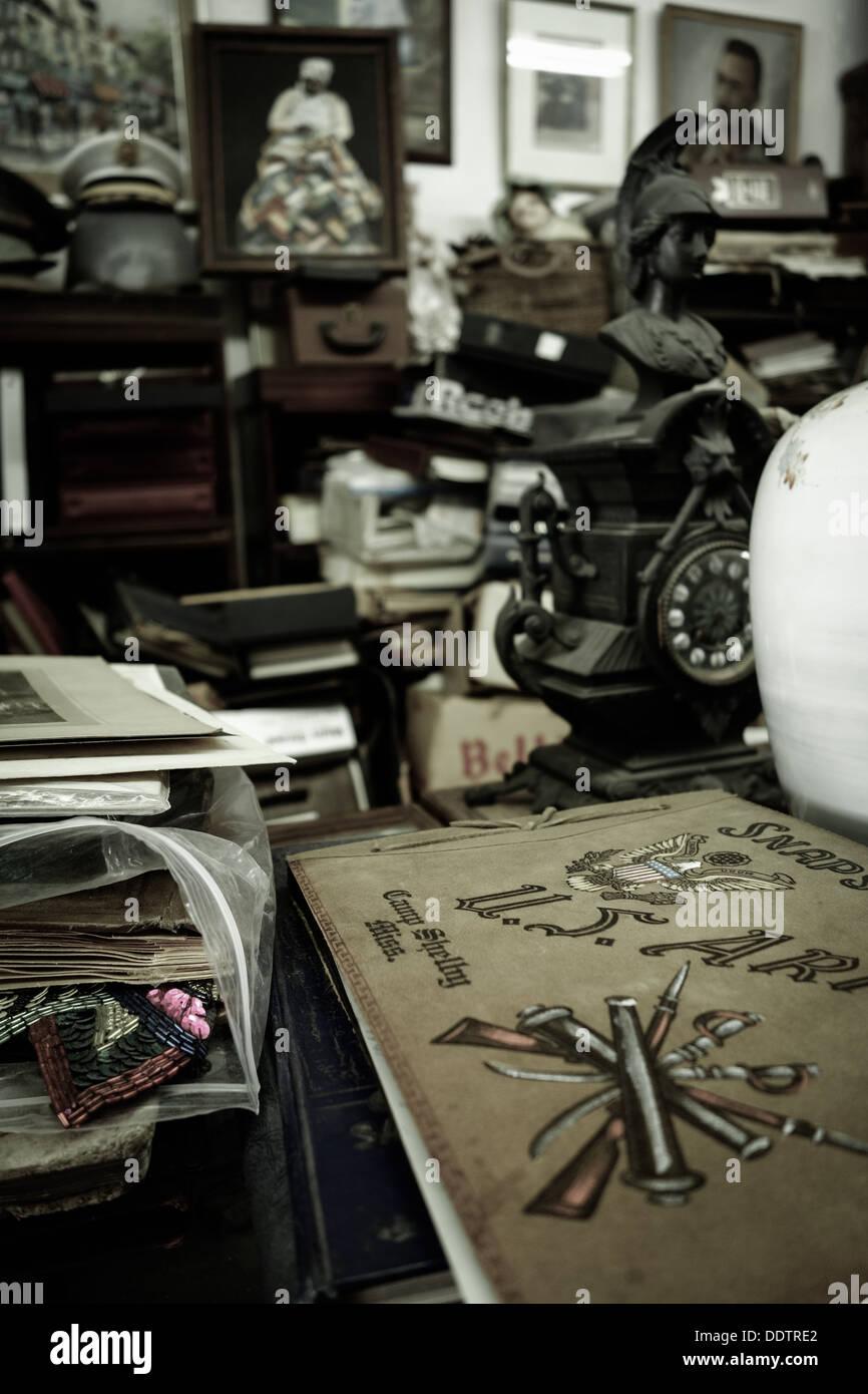 Un vieil album de l'armée parmi beaucoup d'autres objets vintages dans une boutique d'antiquités Photo Stock