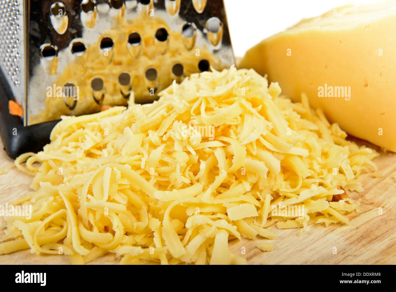 Fromage râpé sur une planche à découper Photo Stock