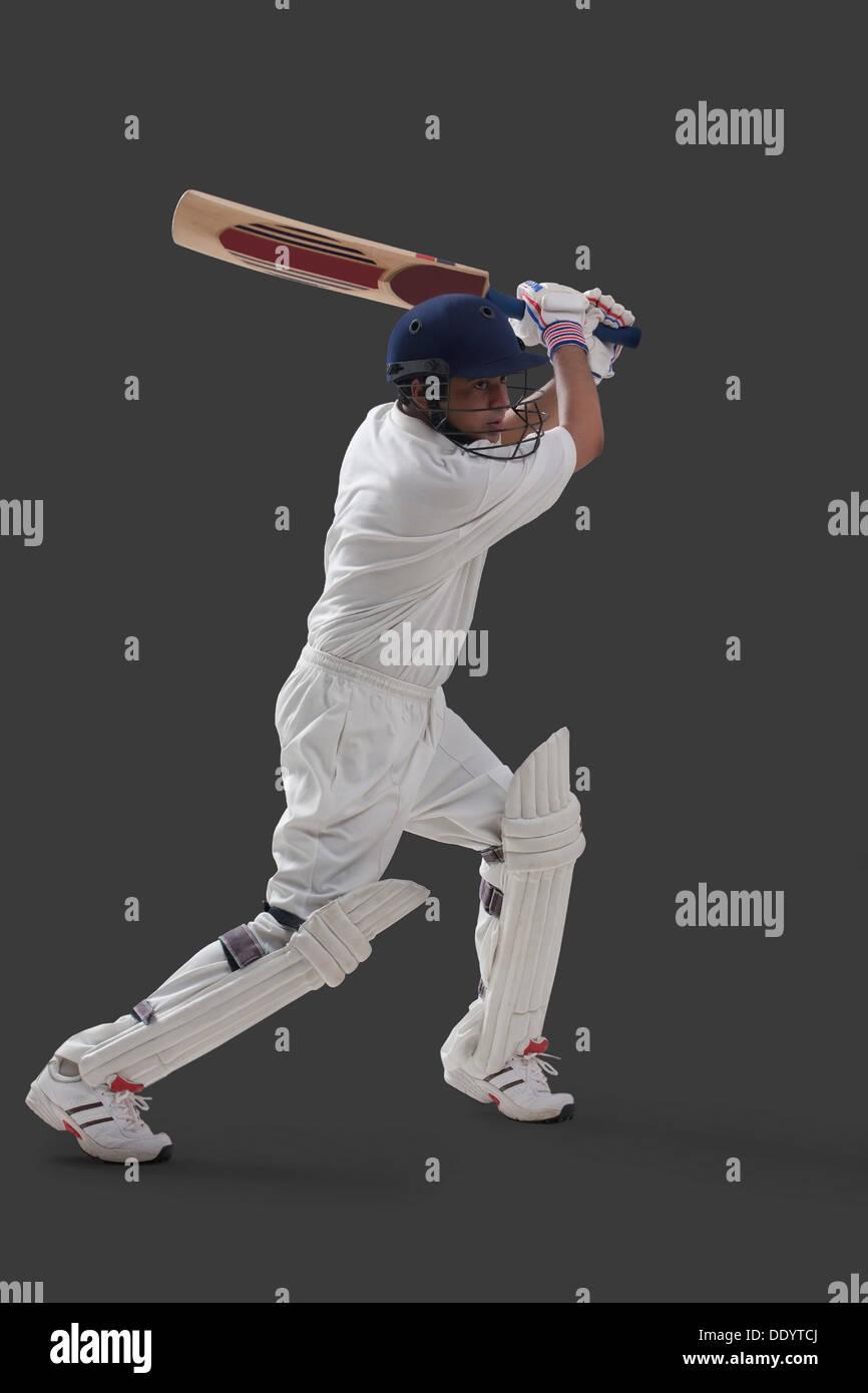 Jeune homme player jouer au cricket sur fond gris isolé Photo Stock