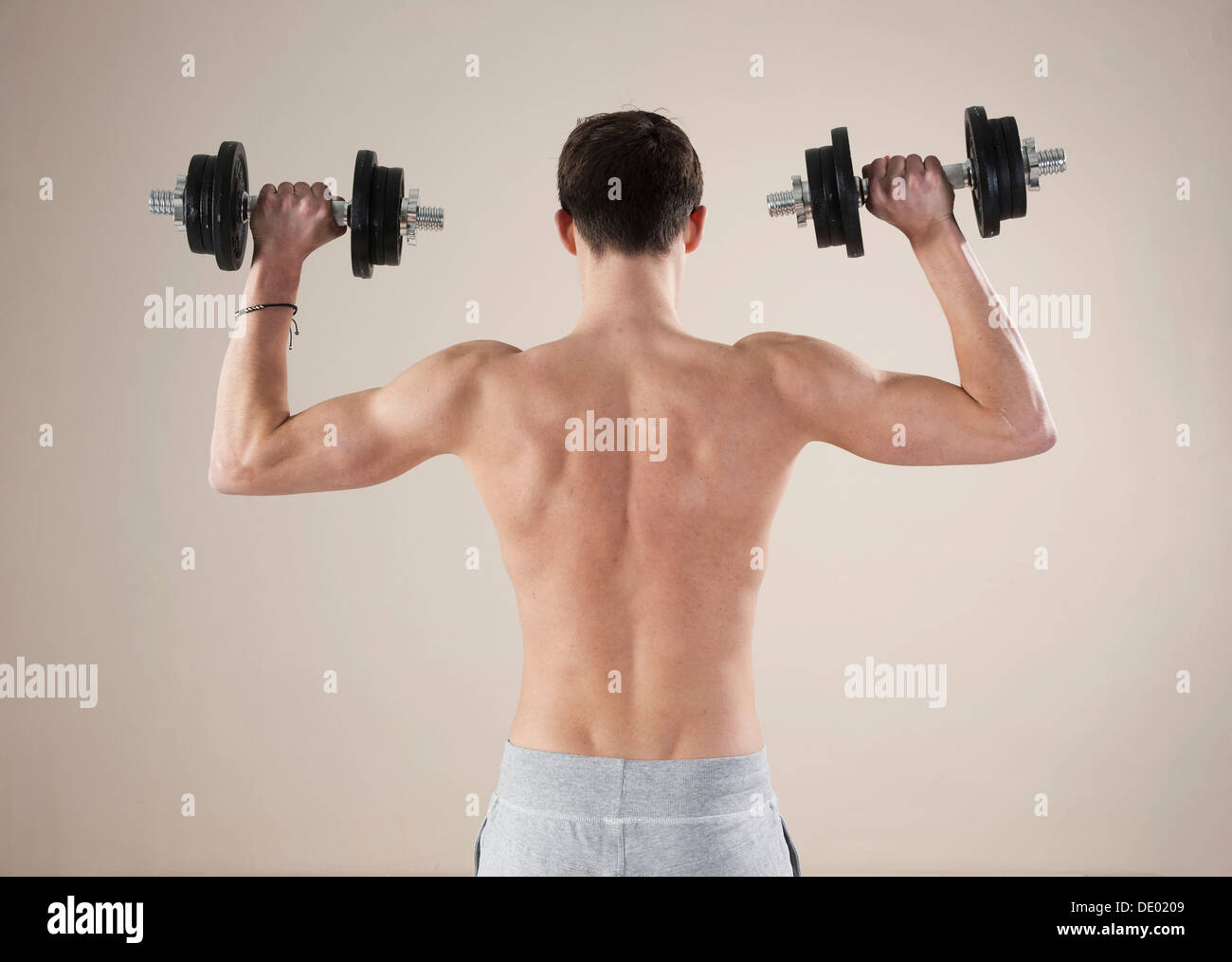 Jeune homme faisant la formation de poids avec haltères Photo Stock