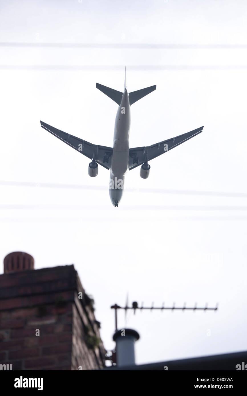 Vol d'un avion à basse altitude au-dessus du toit de la chambre. Photo Stock