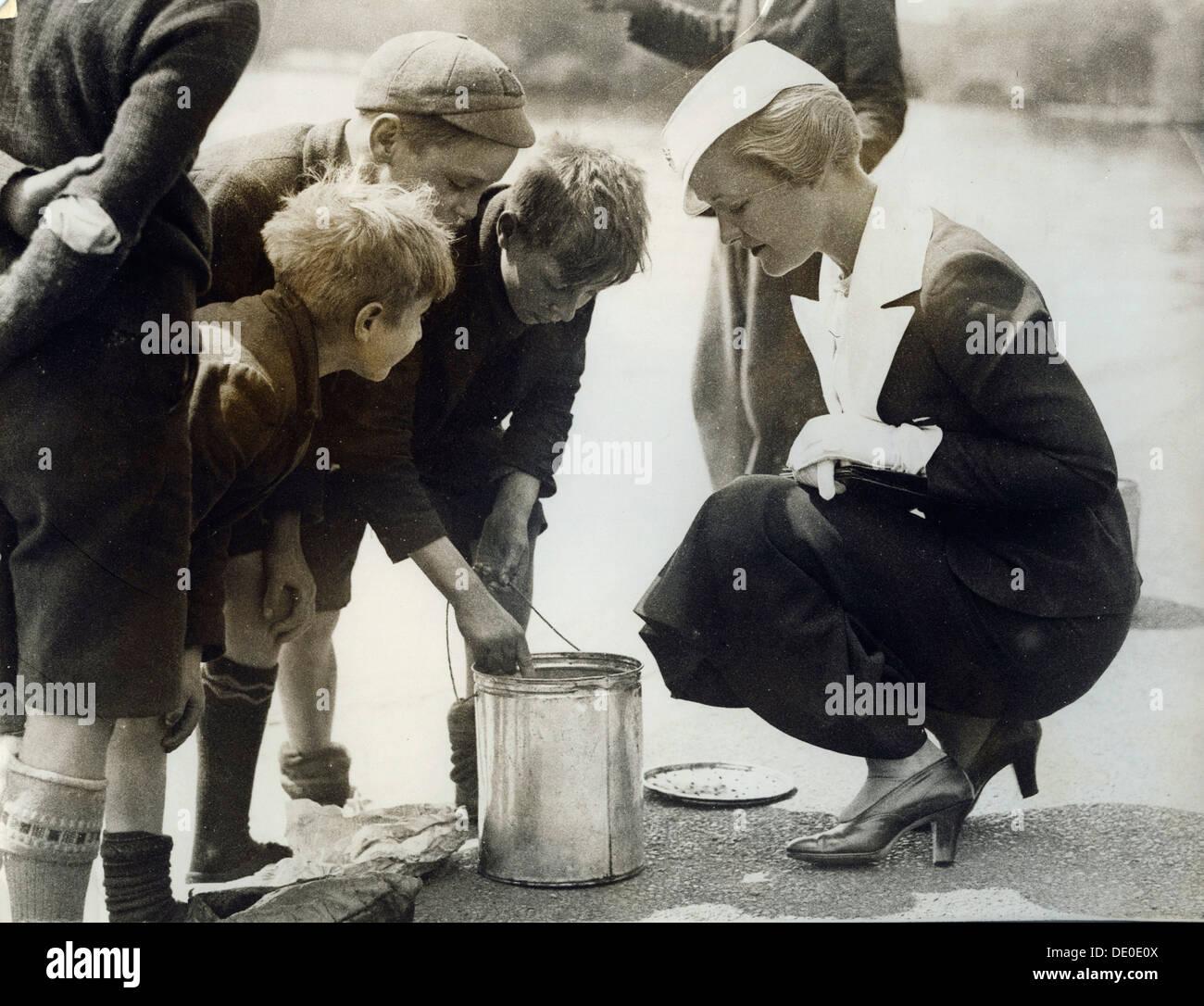 Laura La Plante, actrice et star du film, 1934. Laura La Plante (1904-1996) est surtout connu pour ses rôles dans les films muets. Ici on la voit tandis qu'à Londres à la recherche d'une offre de films. Elle a séjourné à Londres pour trois semaines avant de se rendre à Paris. Elle est avec un groupe de garçons qui avaient été 'capture tiddlers' dans la Serpentine. Photo Stock