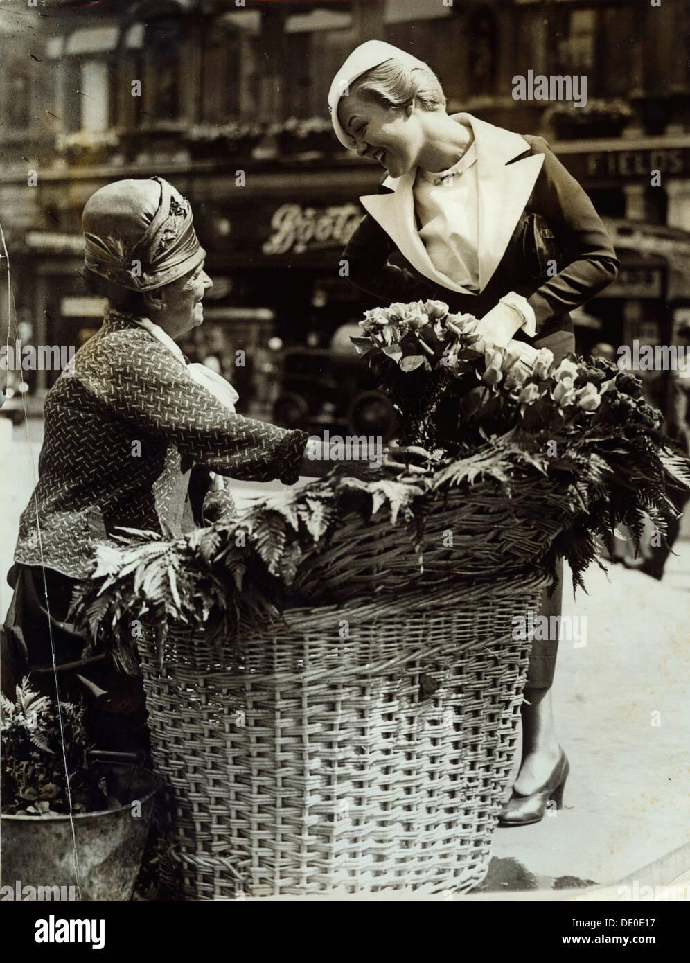 Laura La Plante, actrice et star du film, 1934. Laura La Plante (1904-1996) est surtout connu pour ses rôles dans les films muets. Ici on la voit discuter avec une fille de fleur dans Piccadilly à Londres à la recherche d'une offre de films. Elle a séjourné à Londres pour trois semaines avant de se rendre à Paris. Photo Stock