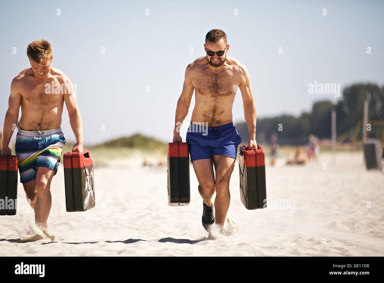 Crossfit solide gars de soulever des poids lourds jerrycans à l'extérieur sur la plage. Les personnes actives en Banque D'Images