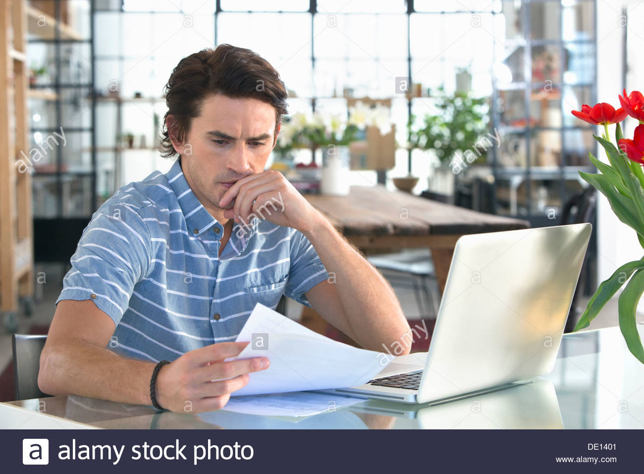 Serious man with laptop looking down at paperwork at kitchen table Photo Stock