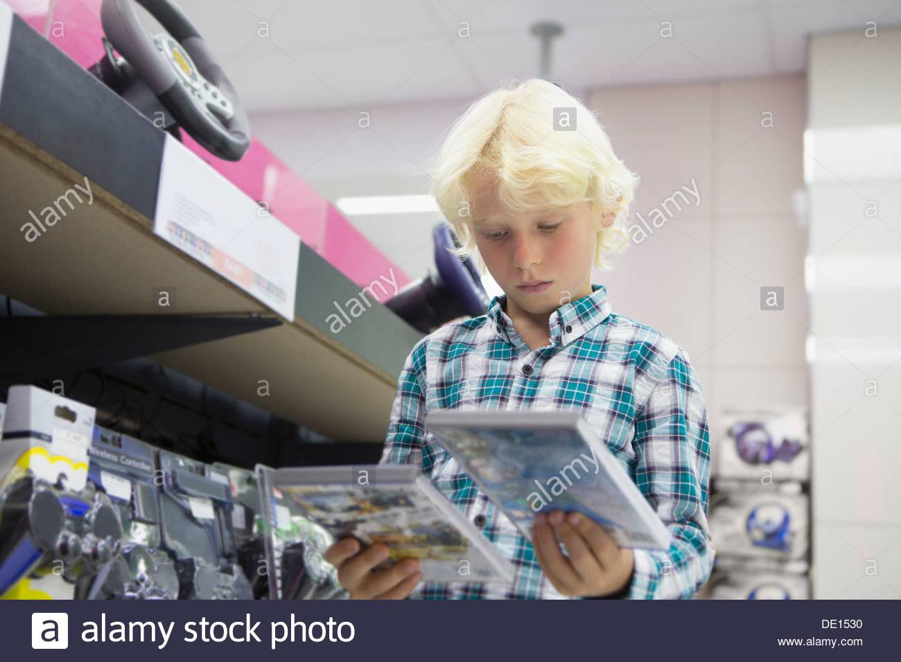 Garçon à la recherche de jeux vidéo au magasin d'électronique Photo Stock