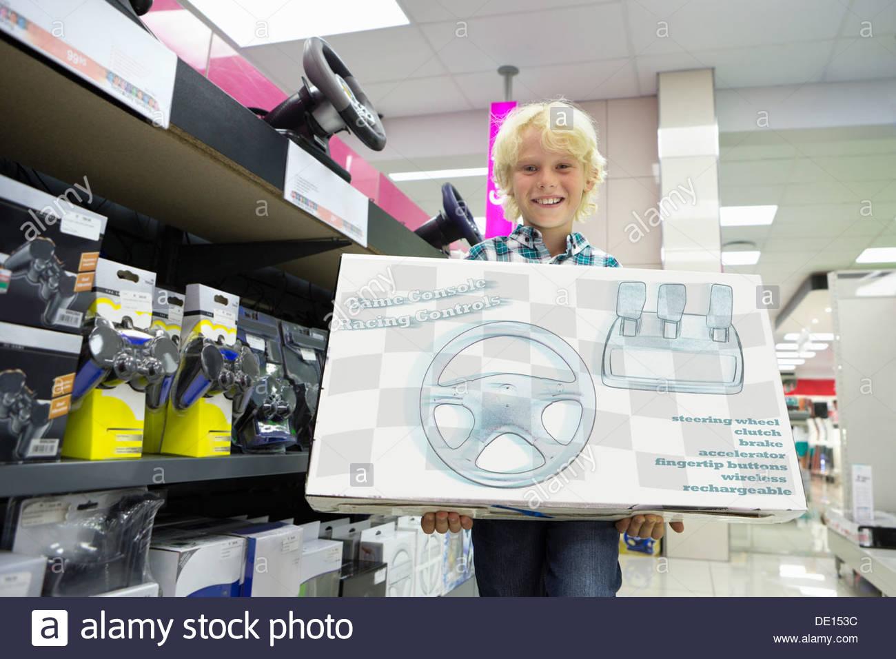 Portrait of smiling boy holding jeu vidéo fort dans votre magasin d'électronique Photo Stock