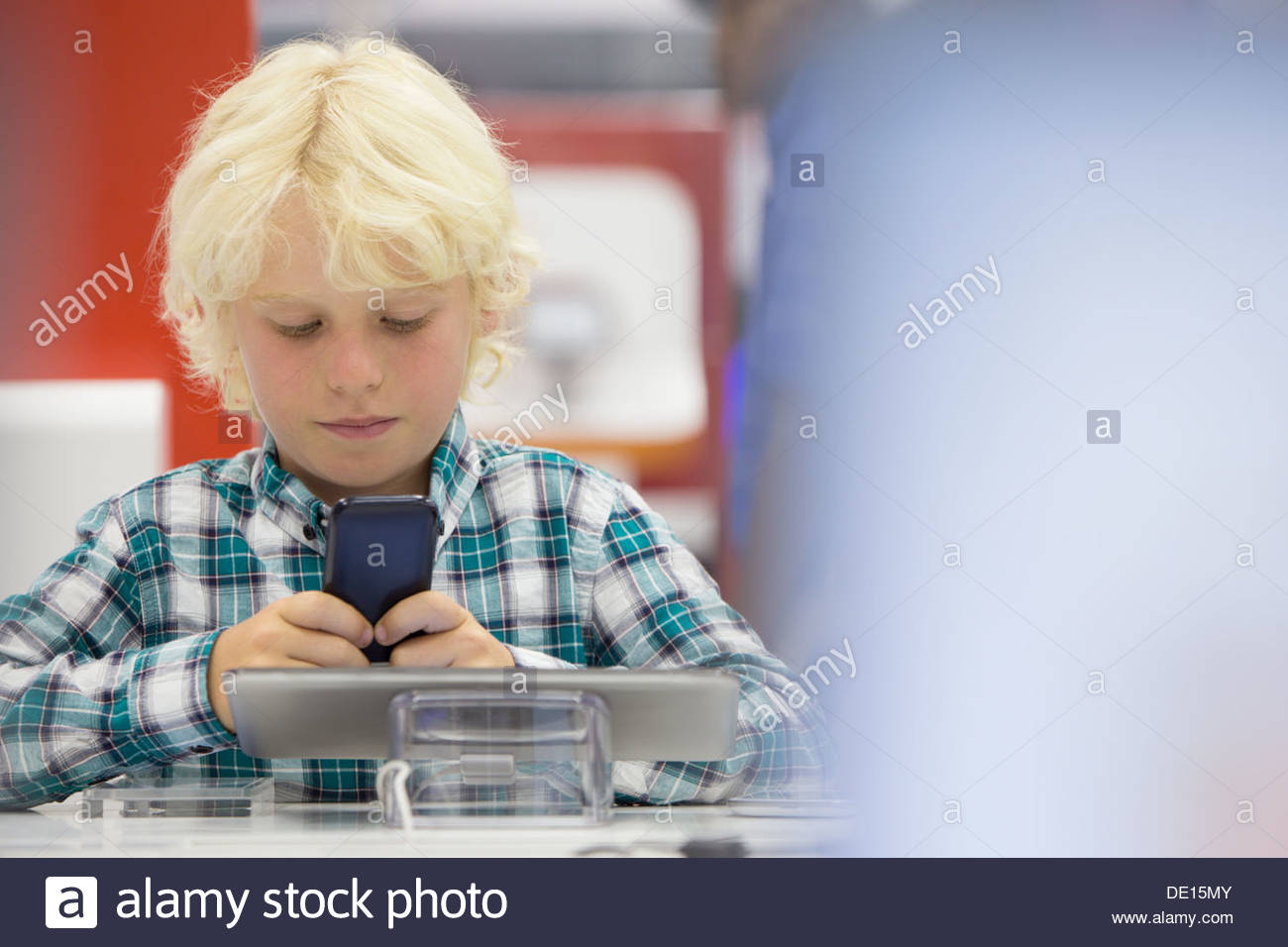Boy looking at cell phone in electronics store Photo Stock