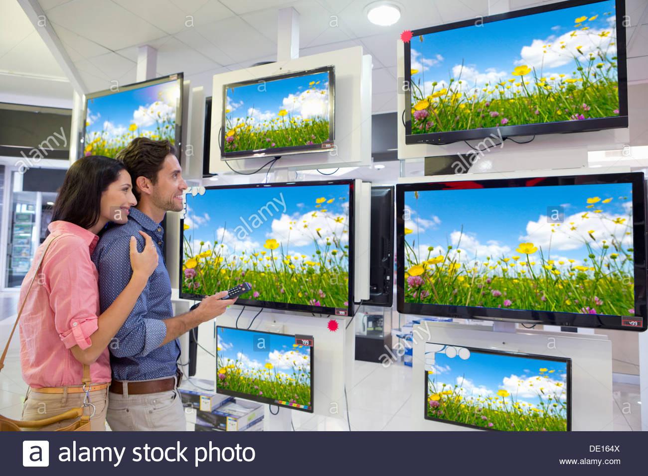 Smiling couple looking at fleurs sauvages sur la télévision à écran plat dans votre magasin d'électronique Photo Stock