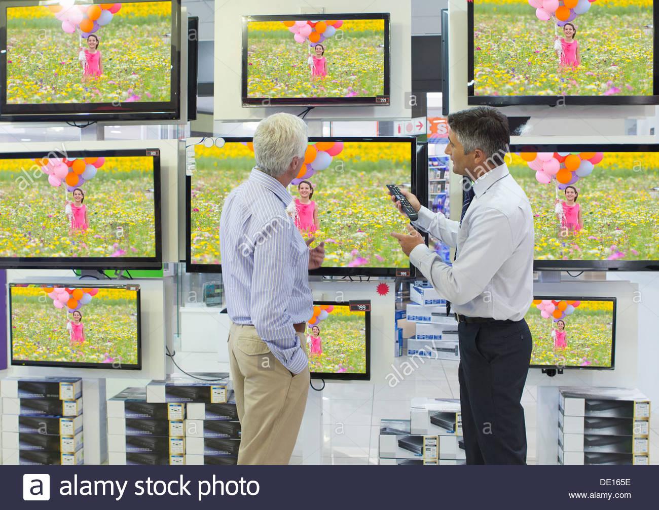 Vendeur montrant senior man d'une télévision à écran plat dans votre magasin d'électronique Photo Stock