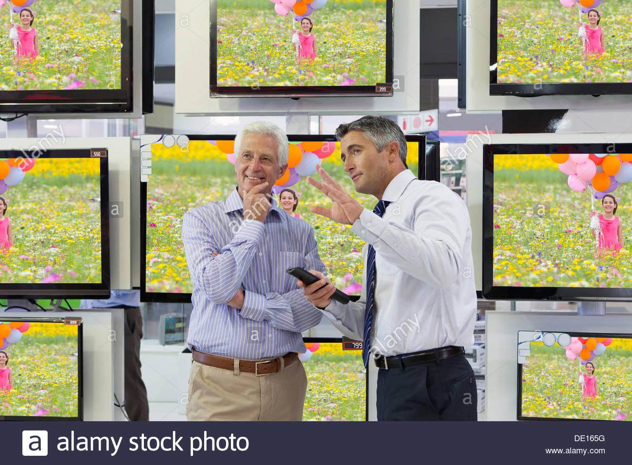 Télévision écran plat derrière et vendeur senior man in electronics store Photo Stock