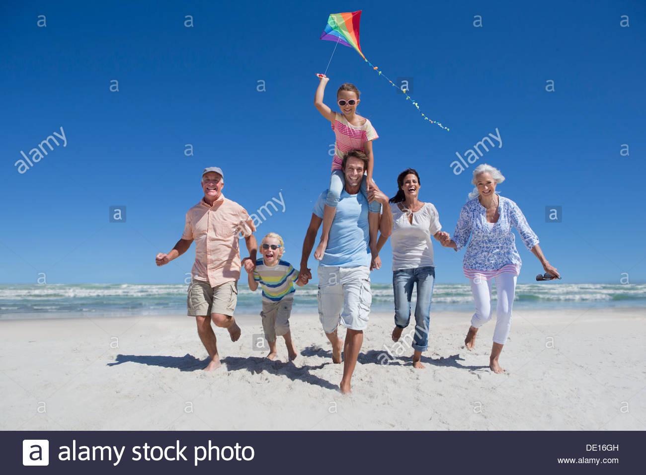 Happy family avec kite s'exécutant sur sunny beach Photo Stock