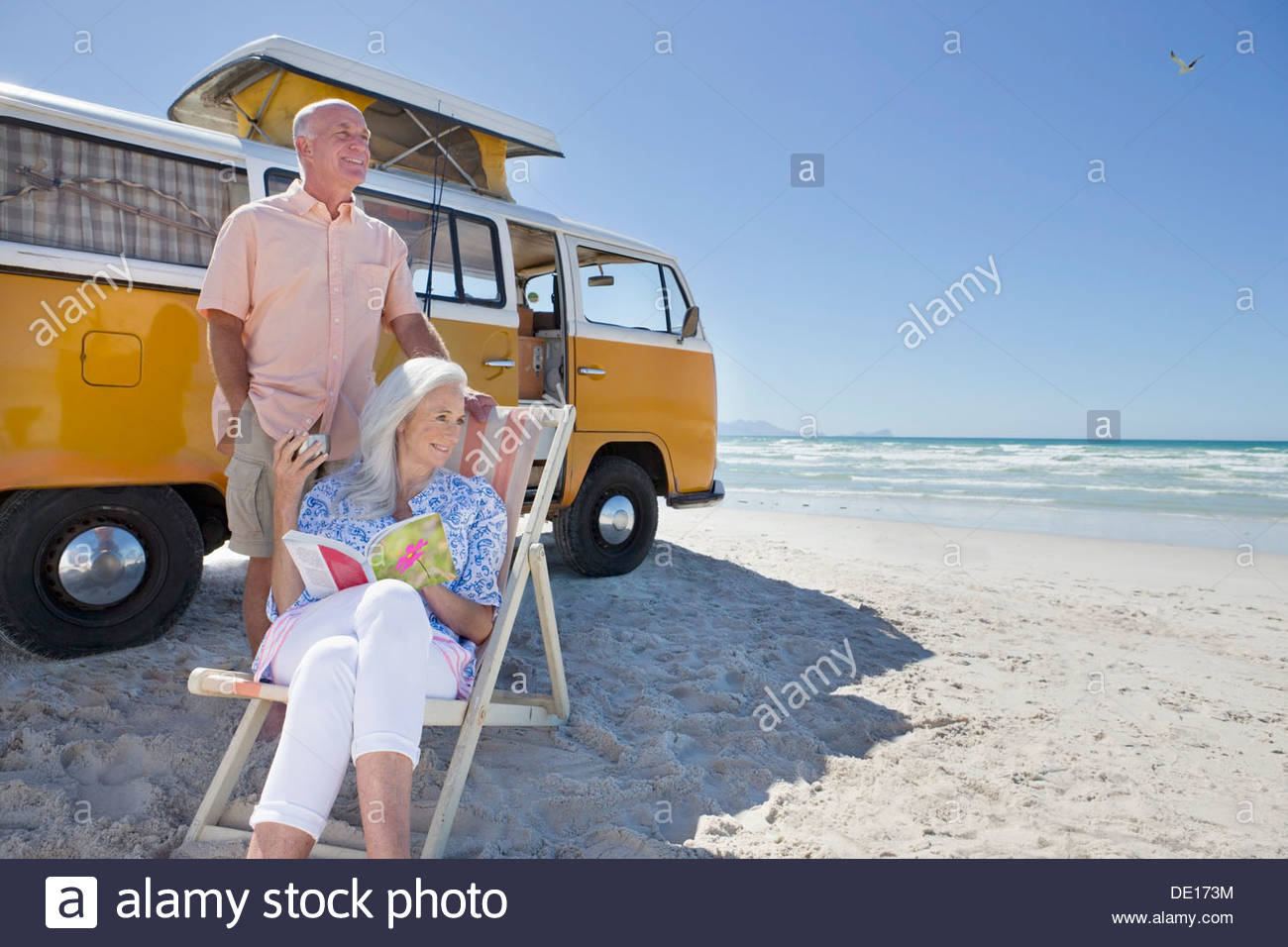 Senior couple relaxing en dehors de van sur sunny beach Banque D'Images