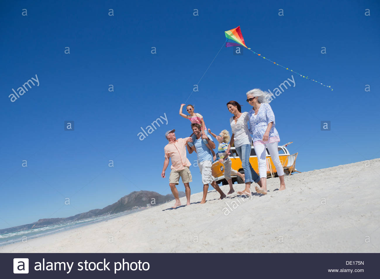 Happy family avec kite walking on sunny beach Photo Stock