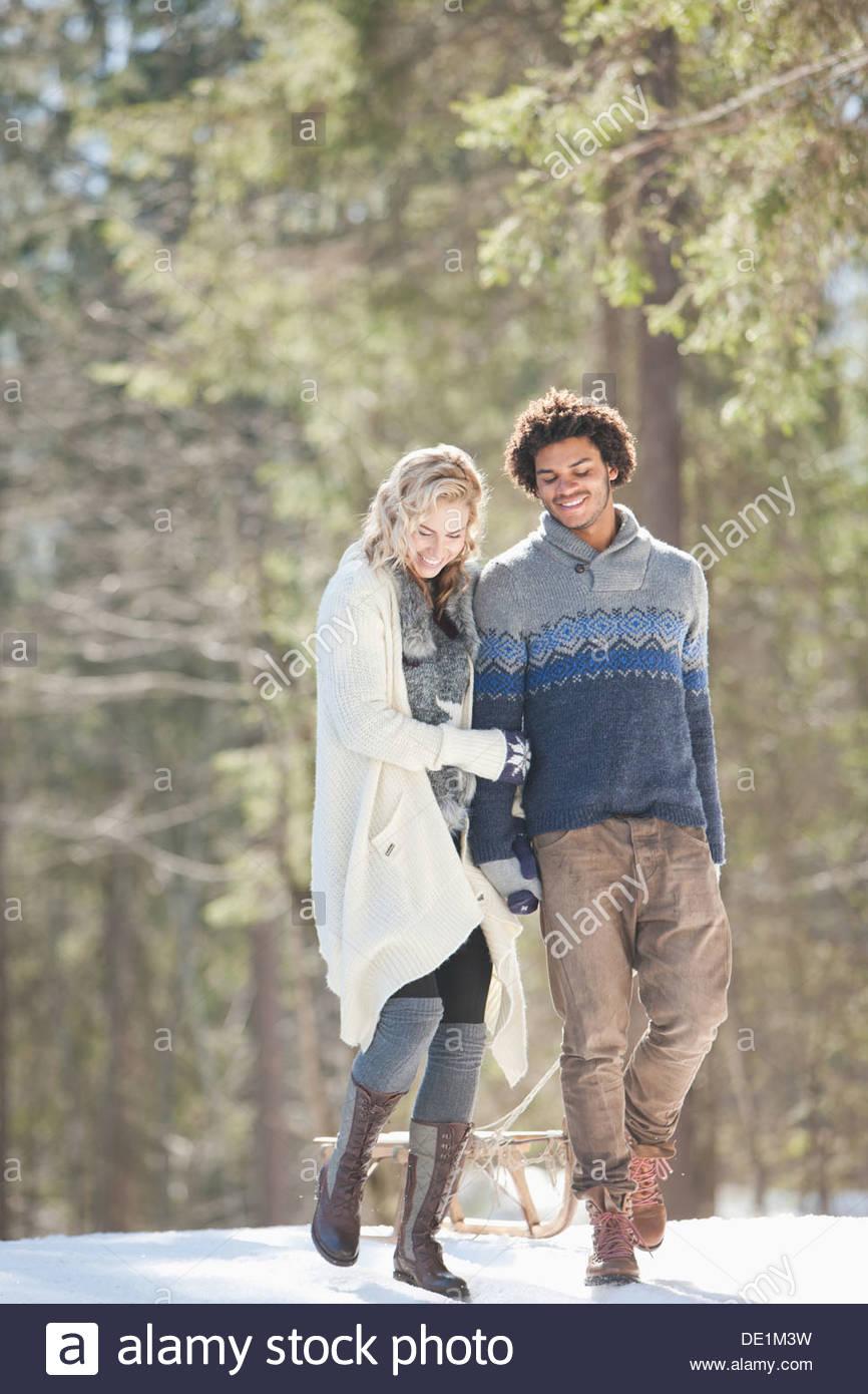 L'homme et la femme avec Sled in snowy landscape Photo Stock