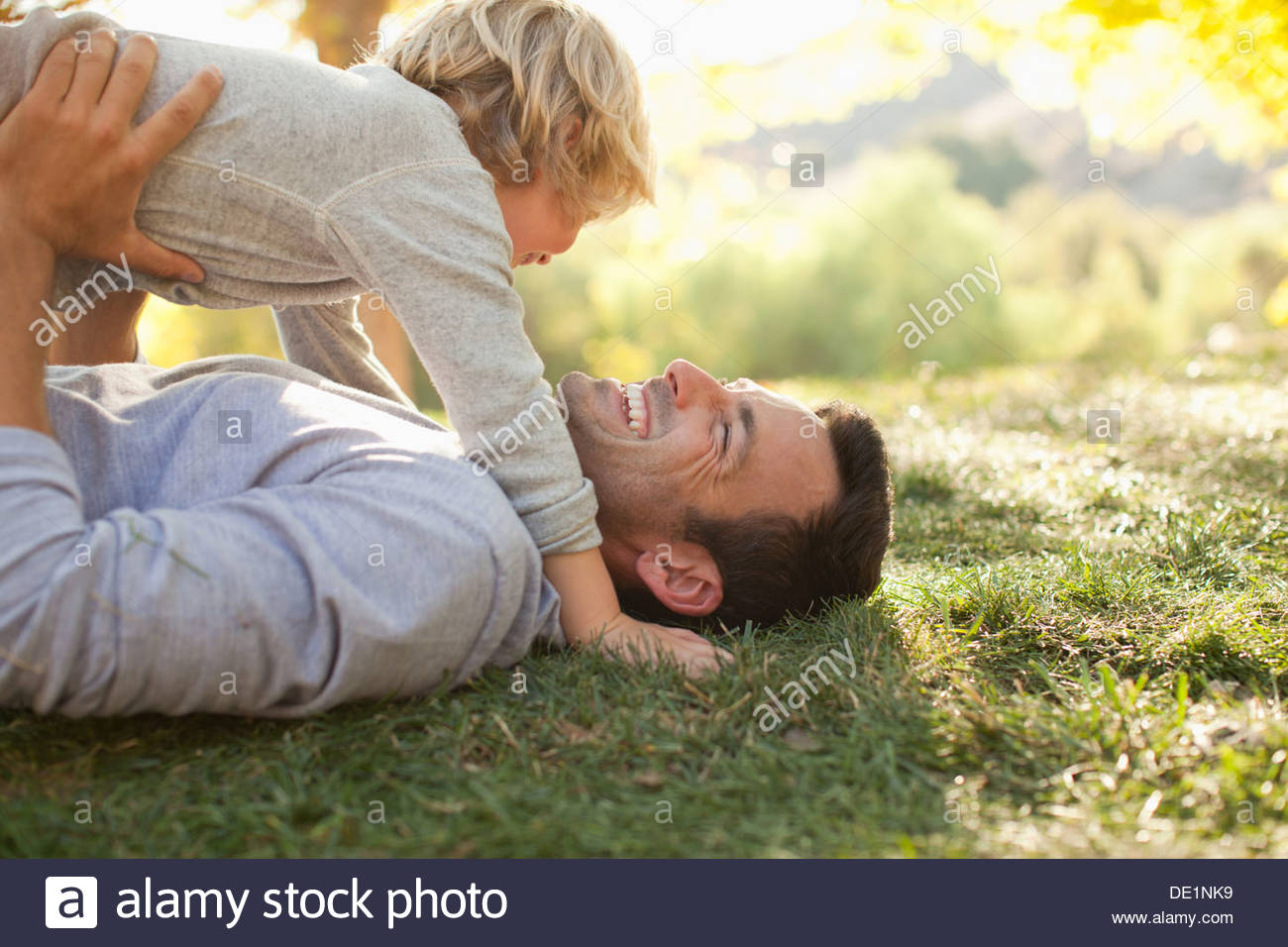Le père et le fils ensemble laying in grass Photo Stock