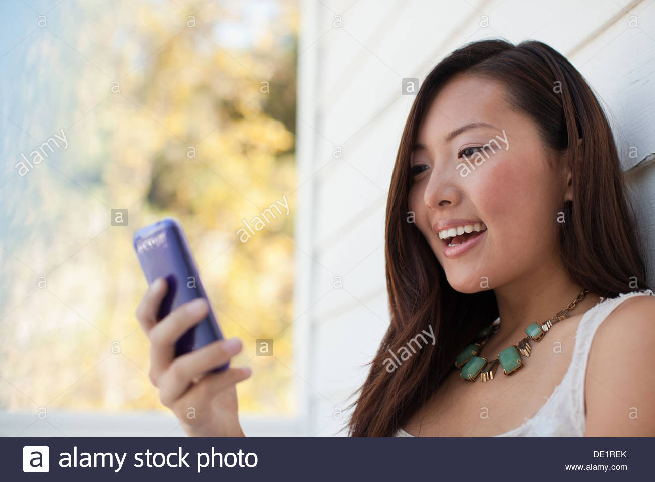 Smiling woman using cell phone outdoors Banque D'Images