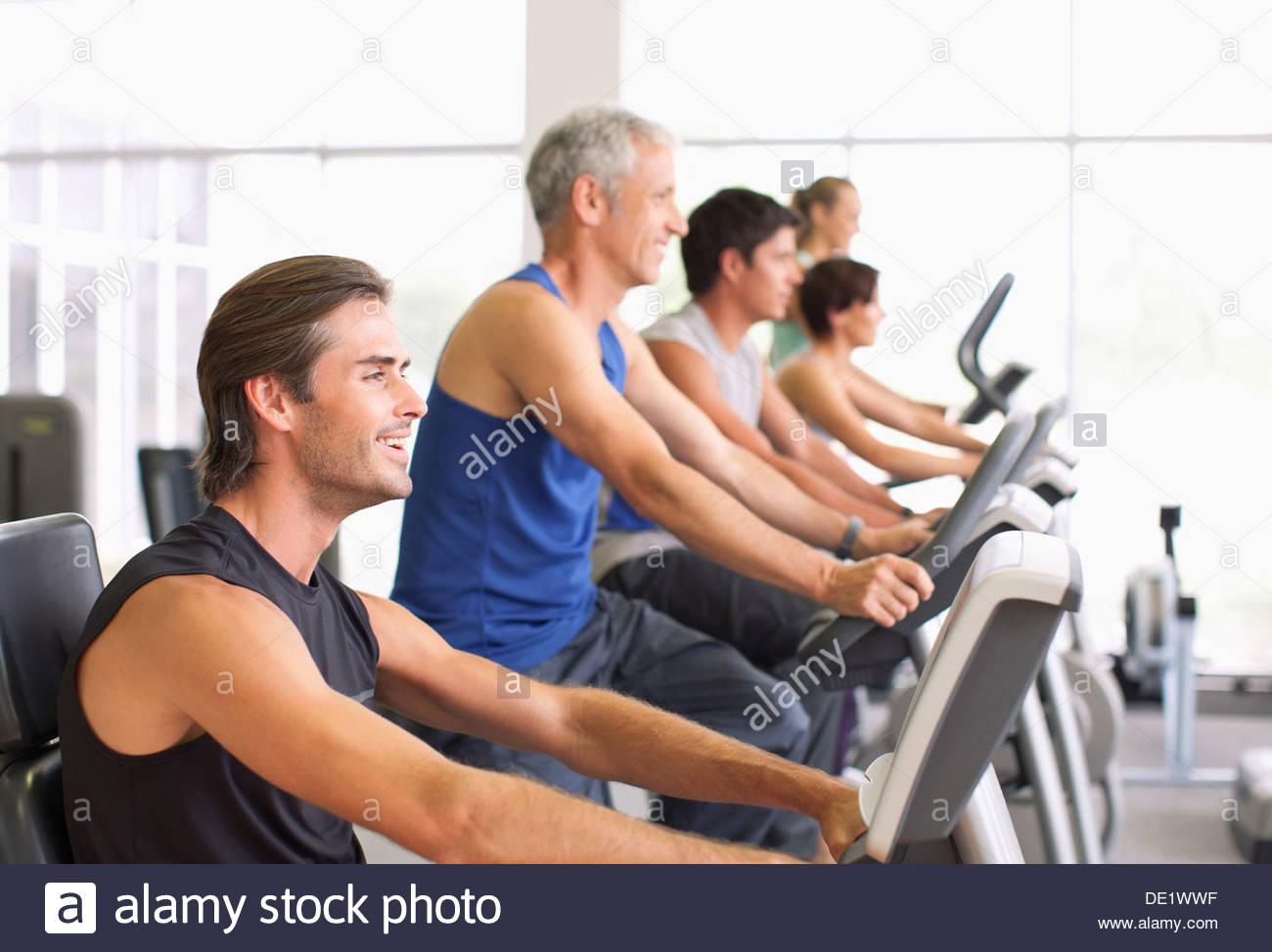 Les personnes travaillant sur des machines d'exercice dans un gymnase Photo Stock
