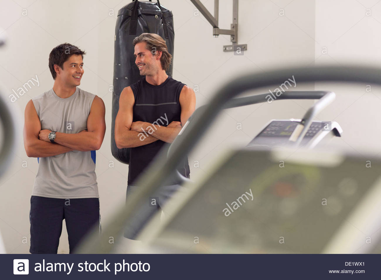 Portrait of smiling men avec les bras croisés en face de punching bag Photo Stock