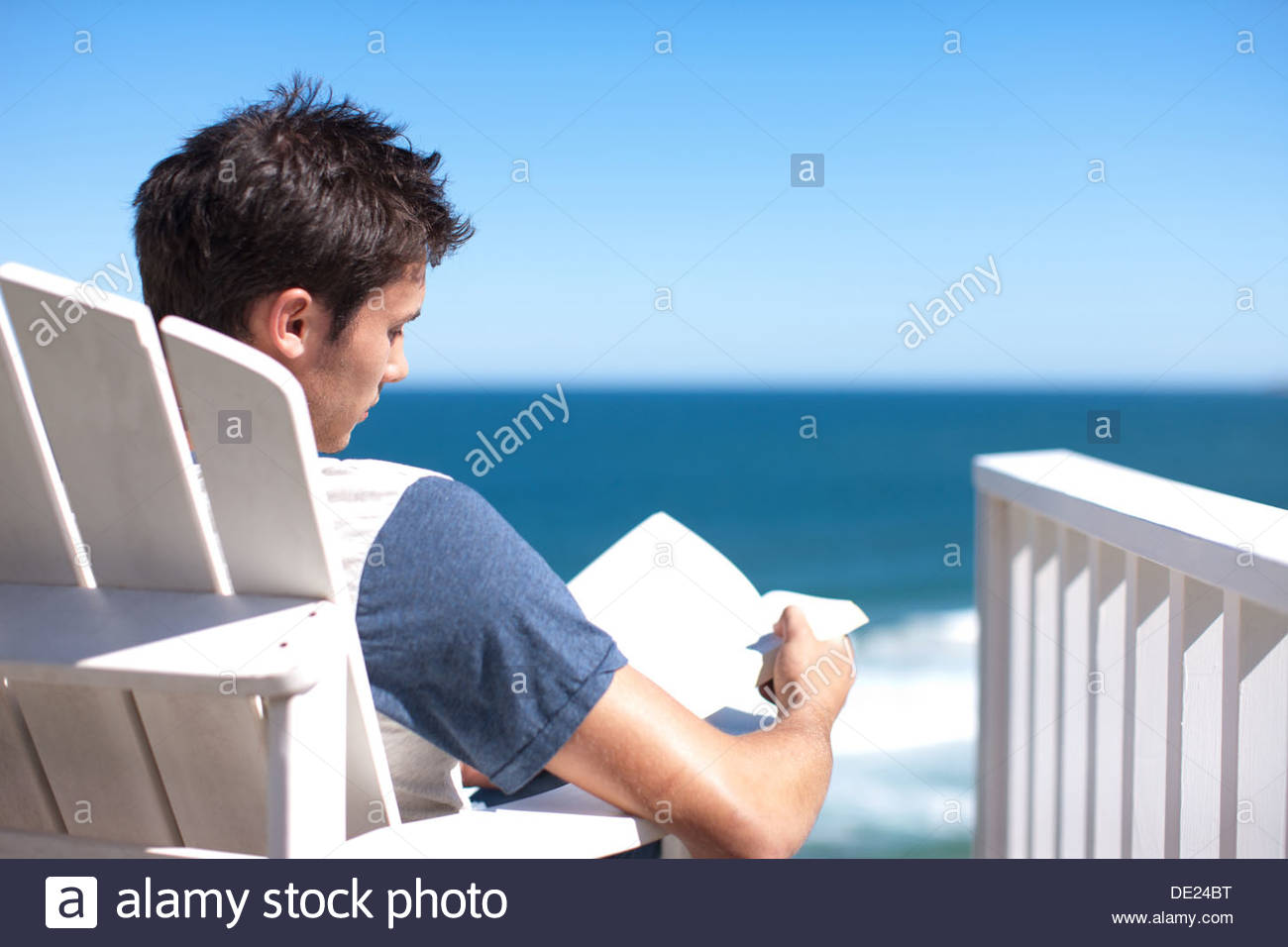 Man reading book in deck chair overlooking ocean Photo Stock