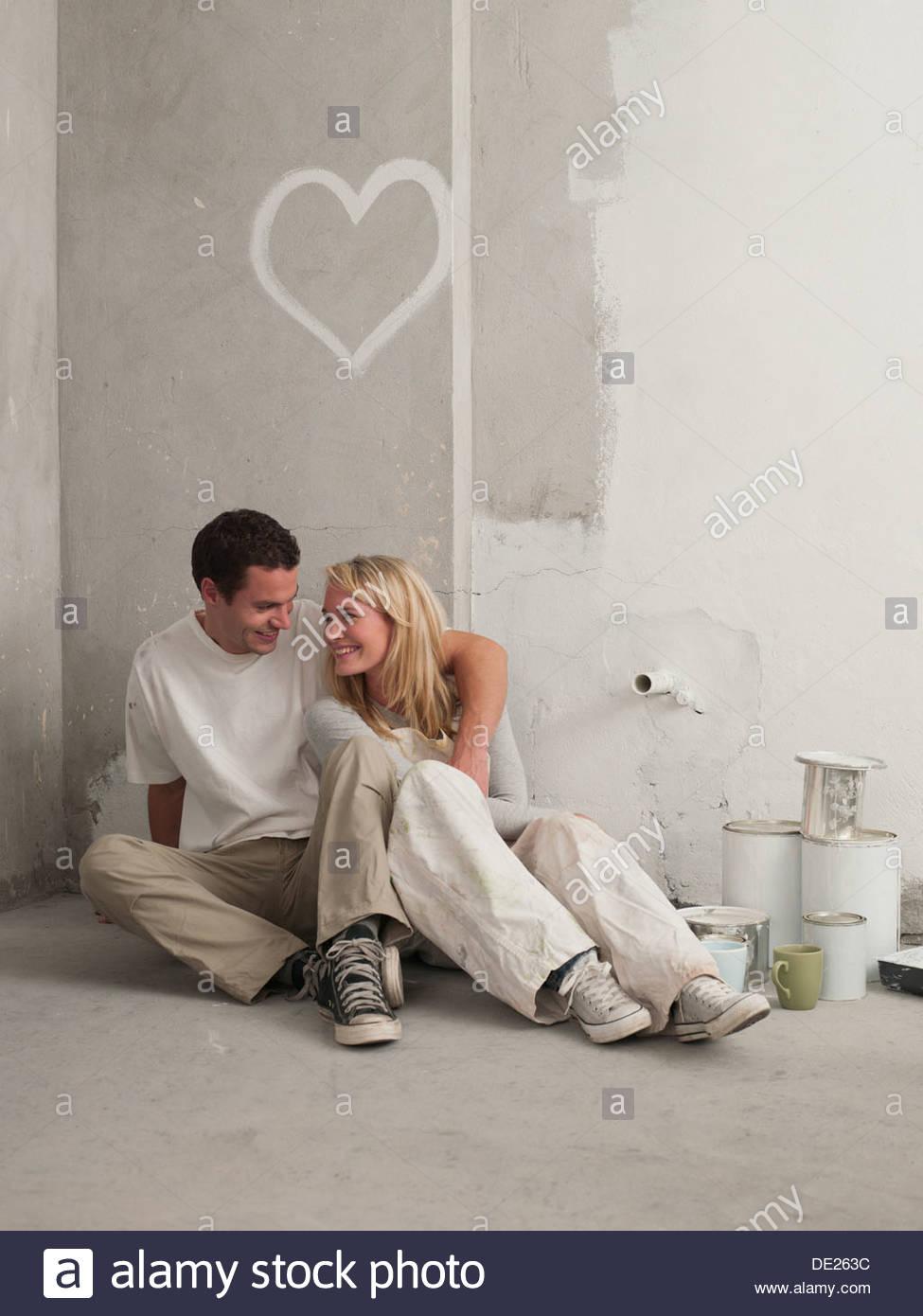 Couple assis sous coeur peint sur mur Photo Stock